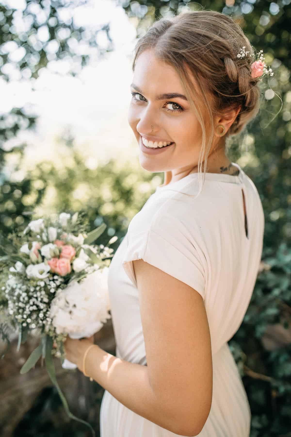 Hochzeitsfotograf im Saarland und der Pfalz - Portrait einer hübschen Braut mit Brautstrauß und Haarschmuck